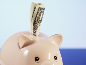 Photo: Close-up of a piggy bank with a one dollar American bank note