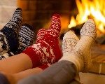 Photo: People's feet in holiday socks by the fire