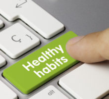 Photo: finger pressing healthy habits text on a keyboard