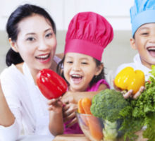 Photo: children with colorful chef's hats and their mom holding colorful fruit