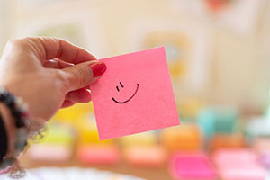 A person's hand holding a post-it note with a smiley face