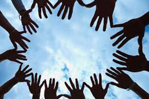 Several hands together making a circle under blue skies