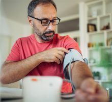 Stock photo of person taking their own blood pressure at home